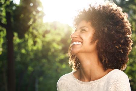 Sluit omhoog zijportret van het mooie zekere vrouw lachen in aard Stockfoto - 84917433