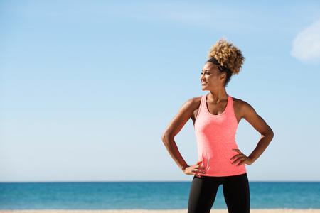 ビーチで立っているフィットの女性の肖像画