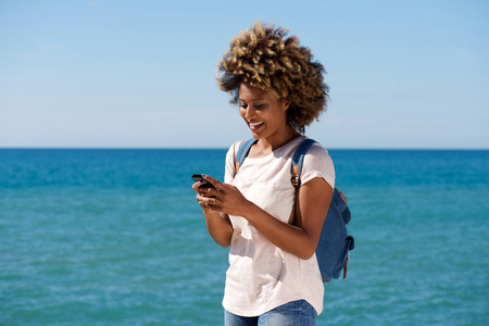 Portrait of smiling african woman on the beach reading text message on smart phone Stockfoto