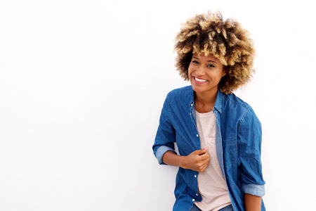 Portrait of attractive young female smiling in blue shirt standing on white background
