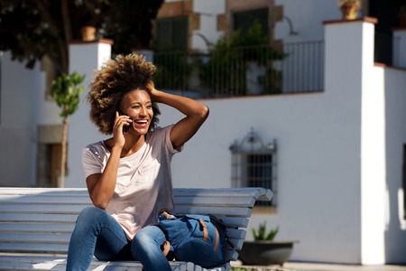 Portrait of happy african woman sitting on a bench and talking on mobile phone