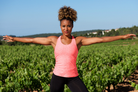 Portrait of healthy young african woman doing stretching exercise outdoors