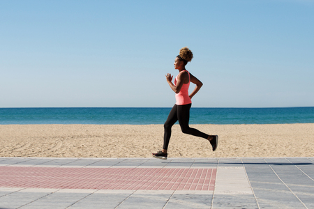 Full length side portrait of fit young african female running by the beach