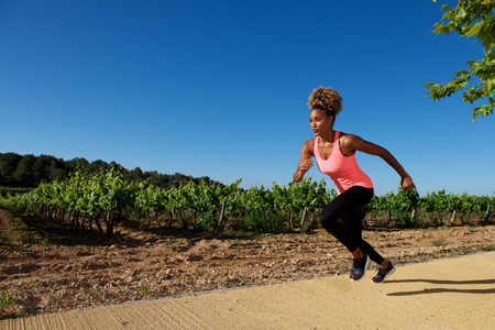 Portrait of fit woman running fast outdoors