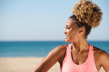 Close up portrait of healthy woman standing on beach and smiling Lizenzfreie Bilder