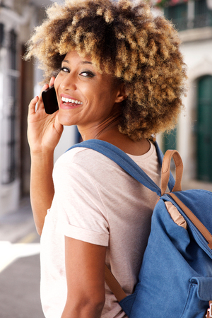 Close up portrait of stylish young black woman standing outdoors and making phone call