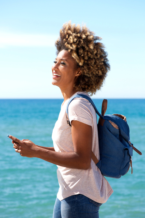 Portrait of young black female tourist along the beach with smart phone