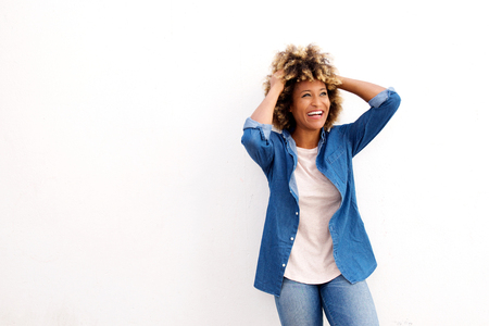 Portrait of laughing african american woman standing against white background