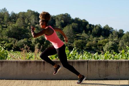 Side portrait of black woman sprinting outdoors Lizenzfreie Bilder