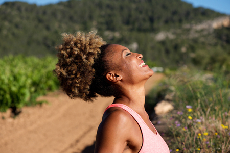 Close up side portrait of healthy young african woman laughing outdoors in morning Lizenzfreie Bilder