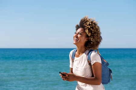 Portrait of laughing young african woman on the beach with mobile phone