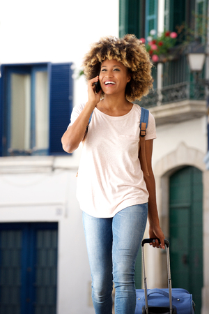 Portrait of beautiful young african woman traveling with bag and talking on smart phone outdoors Lizenzfreie Bilder