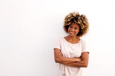 Portrait of beautiful black female standing with arms crossed on white background Lizenzfreie Bilder