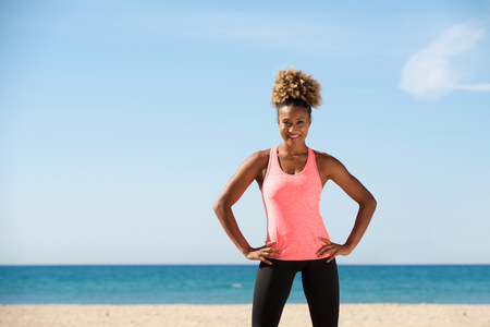Portrait of healthy black young woman standing with hands on hips at the beach Lizenzfreie Bilder