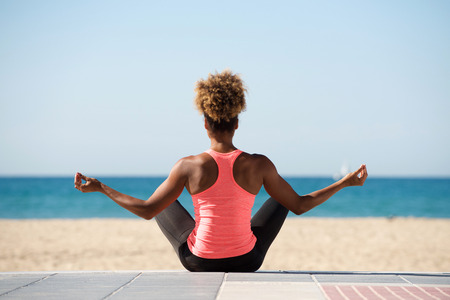 Portrait from behind of young woman doing yoga exercise on seaside Stockfoto