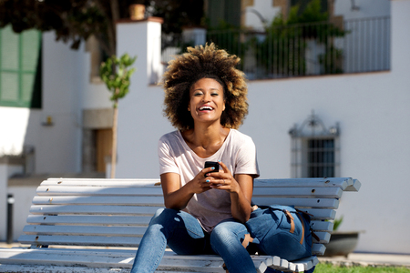 Portrait of beautiful young african woman sitting outdoors on bench with mobile phone and laughing