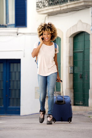 Full body portrait of young female traveling with suitcase and talking on mobile phone outdoors