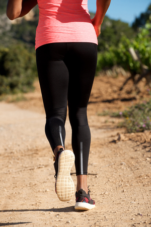 Low section portrait from behind of woman running on dirt road outdoors Stock Photo