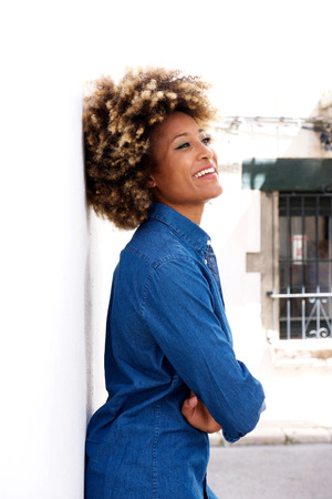 Side portrait of black woman with arms crossed standing by white wall and smiling