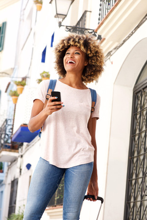 Portrait of smiling african female standing with bag and mobile phone outdoors