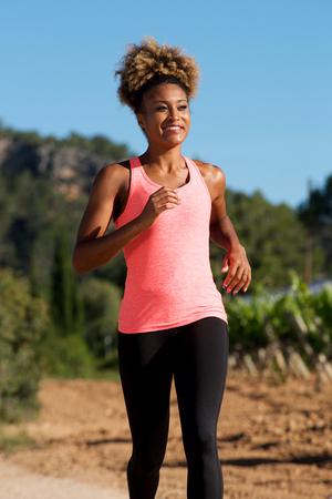 Portrait of afro american female running outside in morning