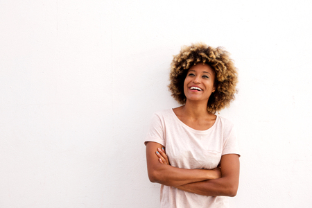 Portrait of smiling afro american woman standing with arms crossed on white background