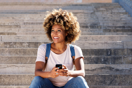Portrait of young afro american female sitting on stairs with mobile phone and looking away