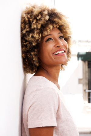 Portrait of african american woman standing against white wall and looking up Lizenzfreie Bilder