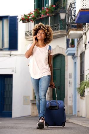 Portrait of smiling young african woman traveling with bag and mobile phone on street