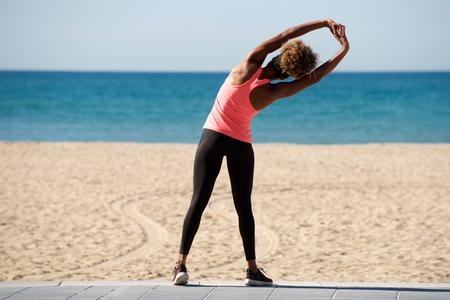 Rear view full length portrait of american woman doing stretching exercise at seaside Lizenzfreie Bilder