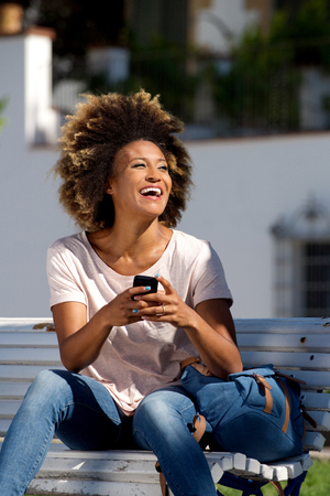 Portrait of attractive african american female sitting outdoors on bench with mobile phone and laughing