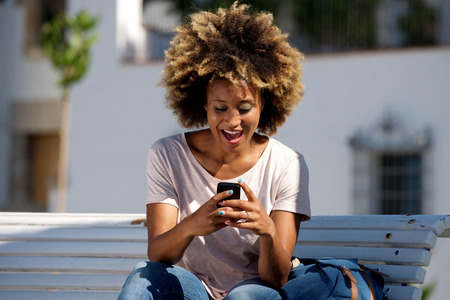 Portrait of laughing young african american female sitting outdoors reading text message on smart phone