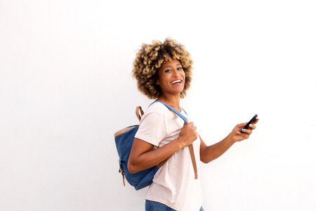 Portrait of modern african woman standing with bag and mobile phone on white background Lizenzfreie Bilder
