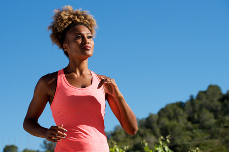 Portrait of african american woman runner jogging outdoors