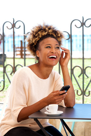 Portrait of young woman sitting in cafe with mobile phone and laughing Lizenzfreie Bilder