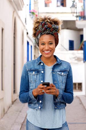 Portrait of beautiful young african woman standing outdoors with smart phone Lizenzfreie Bilder