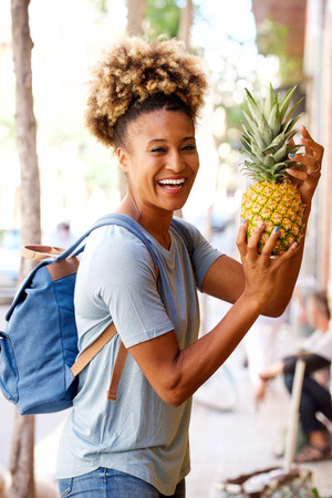Portrait of laughing black woman standing outdoors with pineapple Lizenzfreie Bilder