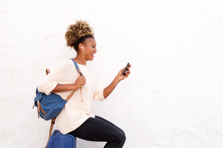 Side portrait of smiling young african woman sitting on suitcase and looking at phone
