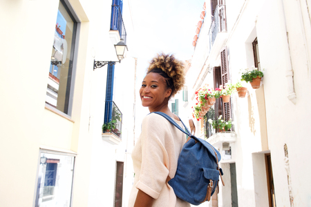 Portrait of smiling african female walking on the narrow street with bag