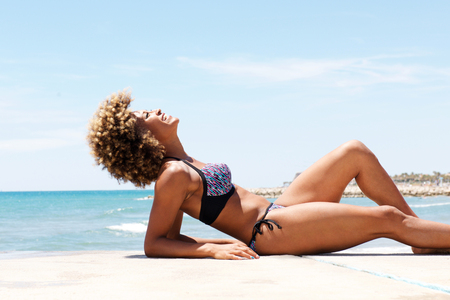 Side portrait of attractive black woman lying on the beach and sunbathing