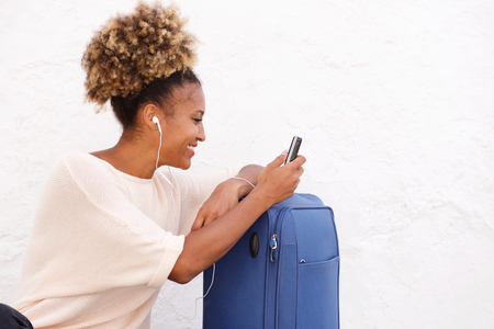 Side portrait of african woman with suitcase using mobile phone against white wall