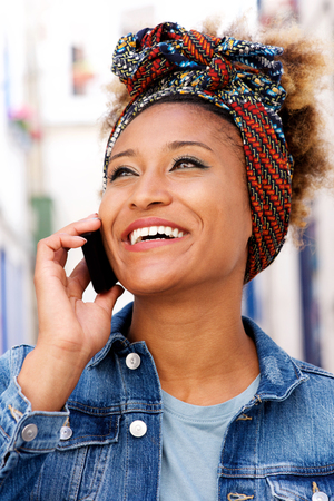 Close up portrait of happy afro american woman with headscarf talking on cellphone outdoors