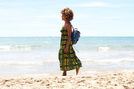 Side portrait of young african woman walking on the beach Lizenzfreie Bilder