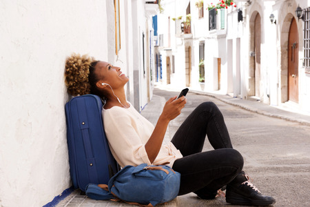Portrait of african american traveler female sitting on sidewalk and listening music from smart phone