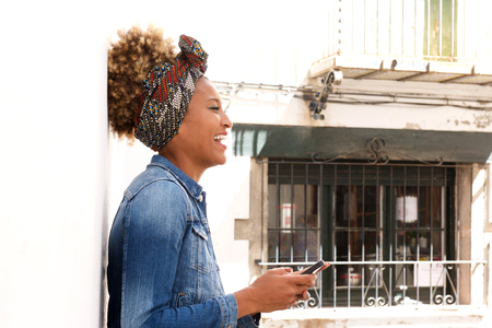 Side portrait of smiling african american woman leaning to a white wall with mobile phone Lizenzfreie Bilder