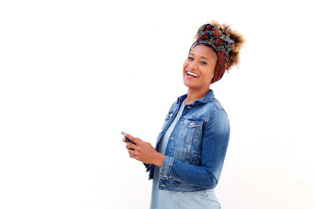 Portrait of african woman with smart phone standing against white background and laughing