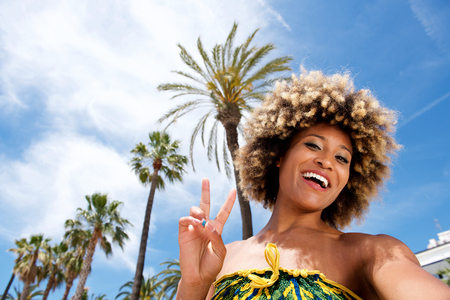 Portrait of beautiful young woman on vacation at the beach taking selfie and gesturing peace sign