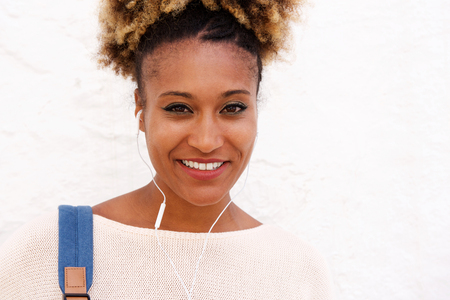 Close up portrait of black woman with earphone standing against white wall