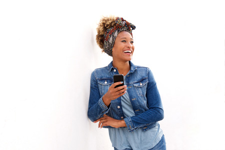 Portrait of stylish black woman standing on white wall with mobile phone and smiling