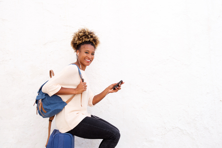 Portrait of african female traveler sitting on suitcase with smart phone